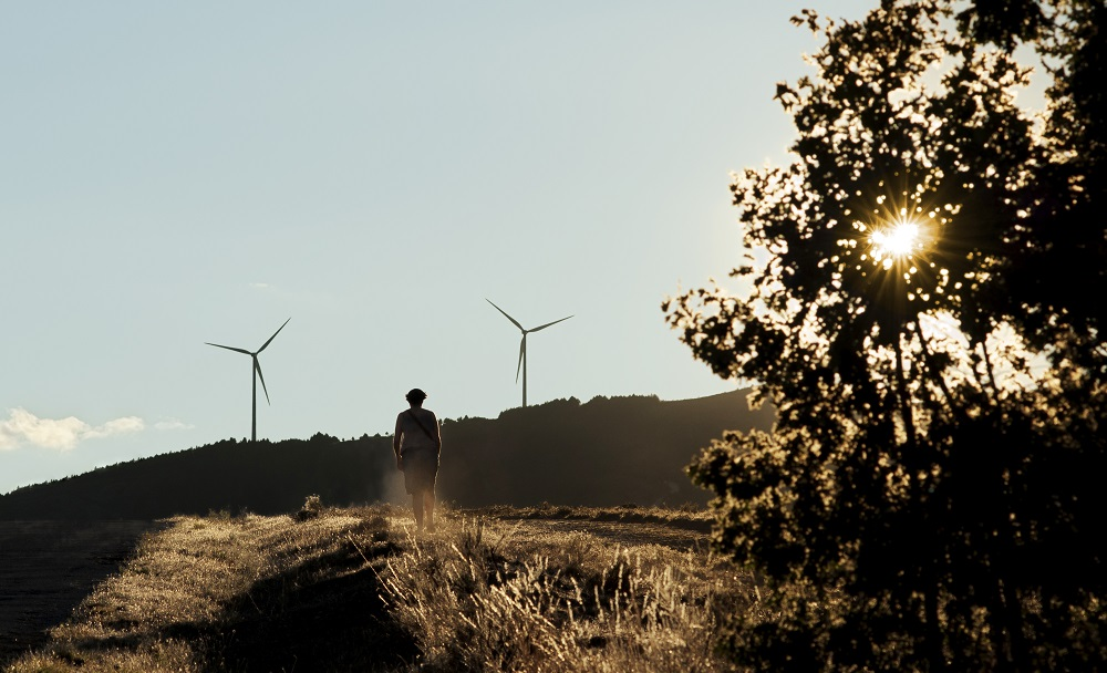 woman walking with wind turbines in the background out of focus