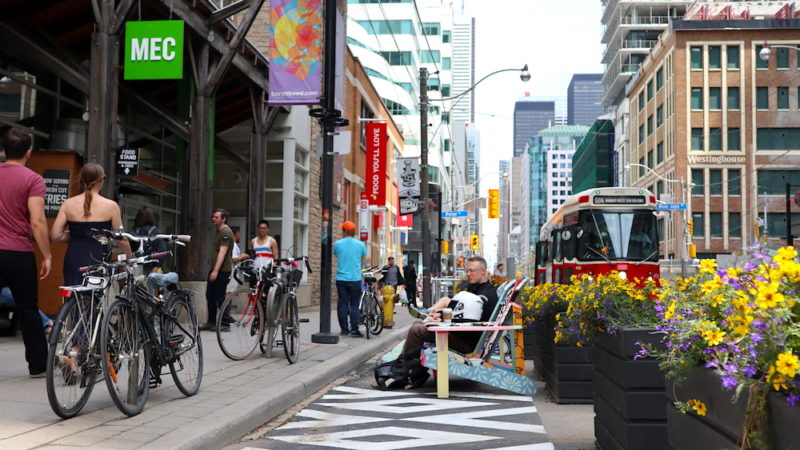 People sitting and walking along King St, with streetcar in background and flowers in foreground.